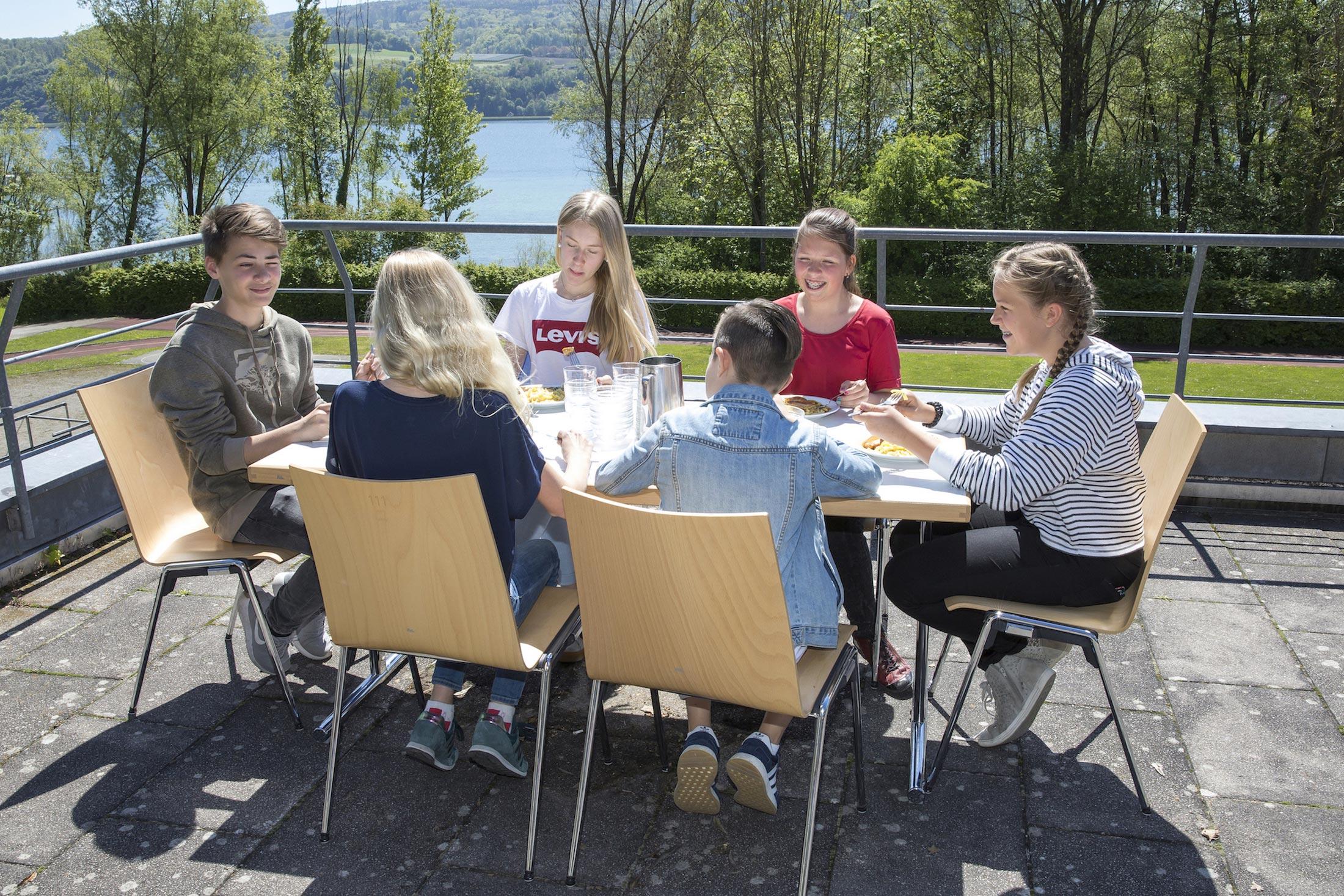Schüler beim Mittagessen auf der Terrasse mit Seeblick